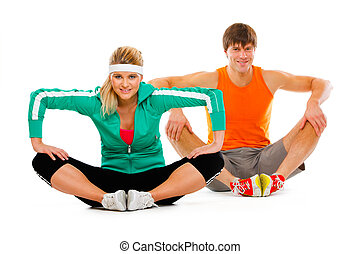 Fitness young woman and man in sportswear doing stretching...