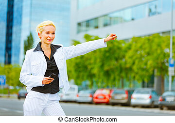 Smiling business woman catching taxi near office center -...