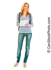 Full length portrait of smiling teengirl with schoolbag writing in notebook isolated on white