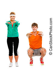 Portrait of healthy girl and man in sportswear sitting on...