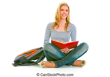 Smiling teen girl with backpack sitting on floor and reading schoolbook isolated on white