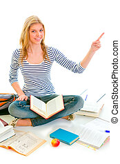 Smiling teen girl sitting on floor among schoolbooks and pointing in corner isolated on white