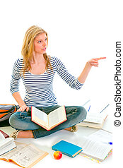 Cheerful teen girl sitting on floor among schoolbooks and pointing in corner isolated on white