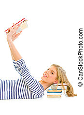 Lying on floor happy teengirl with resting head on pile of schoolbook isolated on white