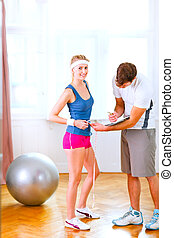 Personal trainer measuring belly of girl in sportswear