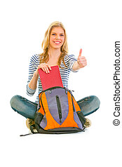 Sitting on floor smiling girl geting book from schoolbag and showing thumbs up gesture isolated on white