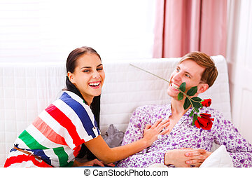 Cheerful young couple having fun time at home