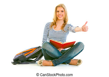 Showing thumbs up gesture smiling young girl with schoolbag and book sitting on floor isolated on white