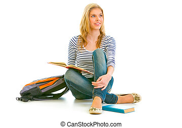 Smiling young girl sitting on floor with schoolbag and books and looking in corner at copy-space isolated on white