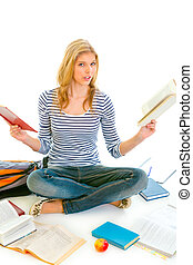 Shocked teen girl sitting on floor with books and  preparing for exams isolated on white