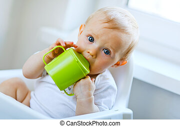 Lovely baby girl sitting in chair and drinking from baby cup...