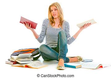 Confused teenager sitting on floor among schoolbooks