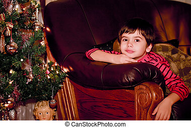 Portrait of an attractive boy near a Christmas tree at night...