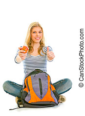 Smiling girl sitting on floor with schoolbag holding apple in hand and showing thumbs up gesture isolated on white