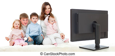 happy family sitting on floor and watching TV or monitor...