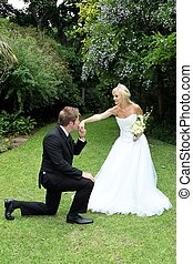 Wedding Couple Kiss - Handsome groom kneeling to kiss his...