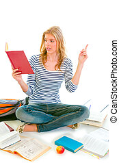 Pensive teenager sitting on floor among schoolbooks and studying isolated on white