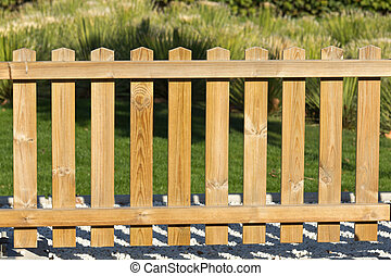 Wooden fence on gravel with green grass lawn behind