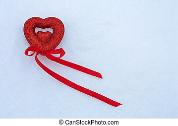 Red heart with ribbon in the snow.