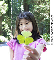 Ten year old girl holding out large three leaf clover - Ten...