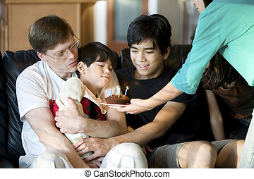 Disabled five year old boy blowing out birthday candles with...