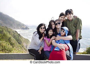 Multiracial family of seven sitting by the Pacific Ocean. Little boy is disabled with cerebral palsy.