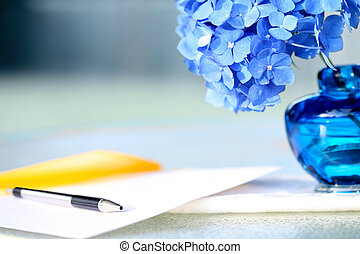 Blue hydrangea flower next to pen and stationery, in a calm...