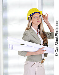 Female engineer with blueprints at business office