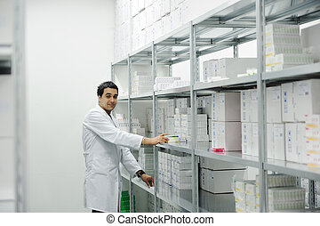 Worker putting boxes together on shelves in modern warehouse