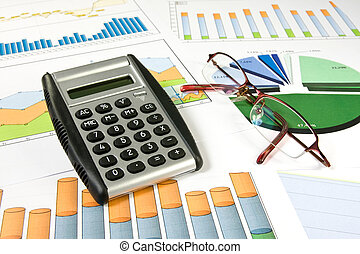 colorful charts, calculator and glasses - business concept....