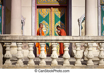 Two young monks meet and salute in buddhist pagoda, Asia -...