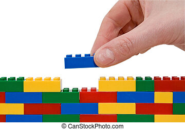 hand building lego - hand building up a wall by stacking up...