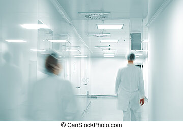 Working people with white uniforms walking in modern factory...