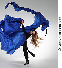 Young blond woman dancing with blue fabric