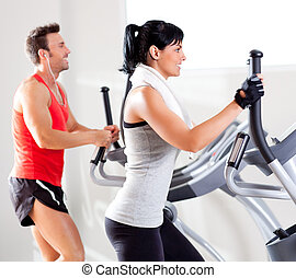 man and woman with elliptical cross trainer at gym - man and...