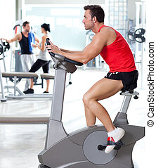 man on stationary bicycle at sport fitness gym interior