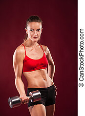 young fit woman lifting dumbell