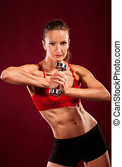 young fit woman lifting dumbell, studio shot