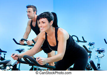 Stationary spinning bicycles fitness girl in a gym sport...