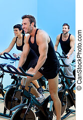Stationary spinning bicycles fitness man in a gym sport club