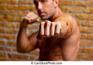 muscle boxer shaped man fist to camera on brickwall
