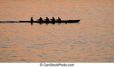 Rowing at sunset - Rowers against sea at sunset