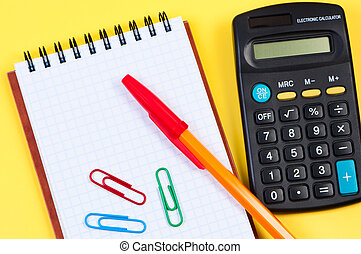 Notepad with pen and paper clips, calculator near.