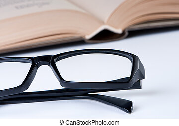 Reading glasses on background of open book.