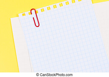 Sheet of paper with paperclip on bright yellow background.
