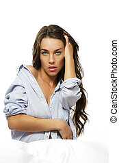 beautiful woman with hand in her hair sitting in bed on white background