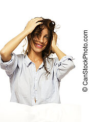 happy woman in pajamas playing with her hair on white background