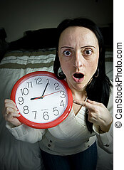 late for work - woman sitting on bed with clock shocked at...