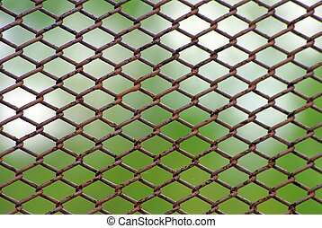 Rusty fence on blue sky - Chain link rusty fence on a green...