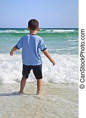 Little boy's First Day at the Beach - Back view of young boy...